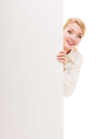 recommending: Advertisement. Happy woman hiding behind blank copy space banner isolated on white. Businesswoman recommending your product