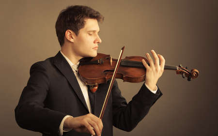 fiddler: Art and artist. Young elegant man violinist fiddler playing violin on brown. Classical music.