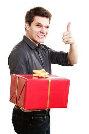 Holiday and special occasion. Young handsome man giving red present gift box with golden ribbon and showing thumb up success hand sign isolated on white. Award surprise. Studio shot. photo