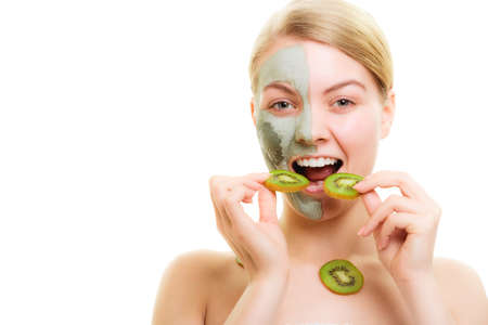 purifying: Skin care. Woman in clay mud mask on face eating kiwi fruit isolated. Girl taking care of dry complexion.