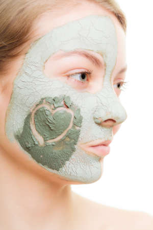 Skin care. Woman in clay mud mask on face with heart on cheek isolated on white. Girl taking care of dry complexion. Beauty treatment. photo