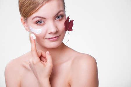 Habitudes beauté. Visage d'une jeune femme avec des feuilles comme symbole de la peau capillaire rouge sur fond gris. Fille de prendre soin de son teint sec appliquer une crème hydratante. traitement de beauté.