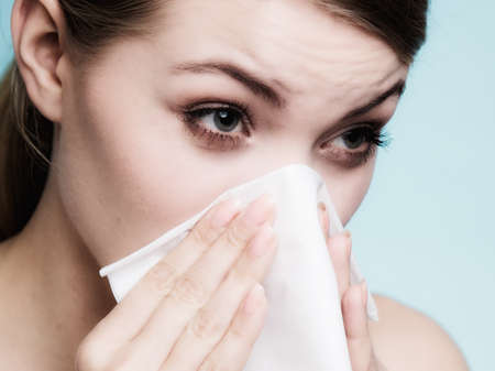allergic: Flu cold or allergy symptom. Sick woman girl sneezing in tissue on blue. Health care.
