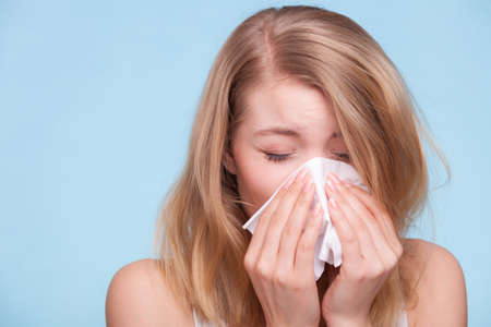 grippe: Flu cold or allergy symptom. Sick young woman girl sneezing in tissue on blue. Health care. Studio shot.
