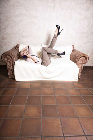 Full length of modern businesswoman woman fashionable girl talking on the mobile phone smartphone lying on the couch. Indoor. photo
