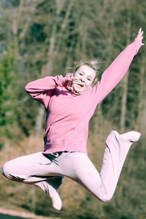 tracksuit: Full length of cheerful woman teenage girl in pink tracksuit jumping high outdoor. Healthy active lifestyle.