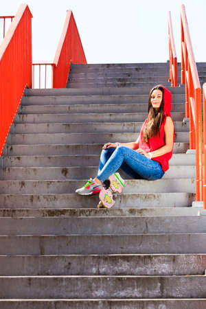 Summer sport and active lifestyle. Cool teenage girl skater with skateboard on the stairs. Outdoor. photo