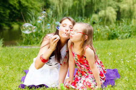 Family happiness and carefree concept. Mother and daughter little girl having fun blowing soap bubbles together in park, green blurred background photo