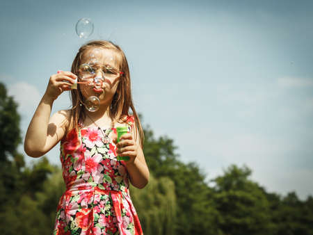 Children happiness and carefree concept. Little girl having fun blowing soap bubbles in park green blurred background photo