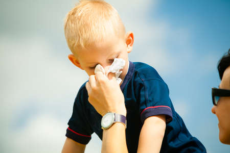 catarrh: Child playing outdoor and blowing nose in handkerchief. Little boy kid sneezing in tissue. Catarrh or allergy to pollen symptom.