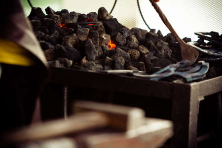 forge: Blacksmith heating up iron, working at an old iron forge.
