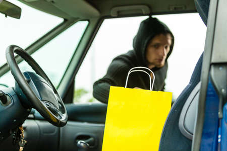 Transportation, crime and ownership concept - thief stealing shopping bag from the car