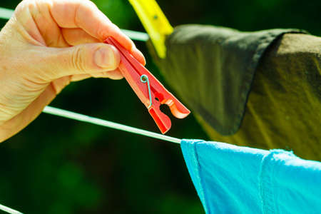 laundry line: Housework. Woman hand hanging clean wet laundry to dry on the rope clothes line outdoor. Stock Photo