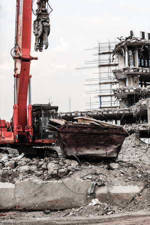 Urban scene. Dismantling of a house. Building demolition and crashing by machinery for new construction. Industry. Stock Photo