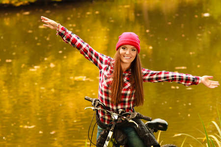 Fall active lifestyle concept,. young woman sporty casual girl relaxing in autumnal park with bicycle, outdoor photo