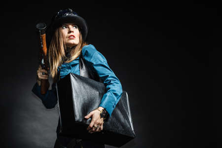 steampunk retro woman with bag suitcase and gun to look back studio shot grunge dark background photo