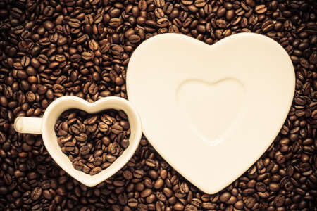 Coffee time. White cup and saucer in shape of heart on roasted coffee beans background. Top view photo