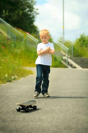 skater boy: Active childhood. Little man skateboarding. Skater boy child playing on park alley with skateboard. Outdoor.