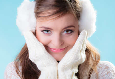 Earmuffs: Winter fashion ear protection. Portrait positive teen girl in warm clothes. Happy woman in white earmuffs and mittens on blue