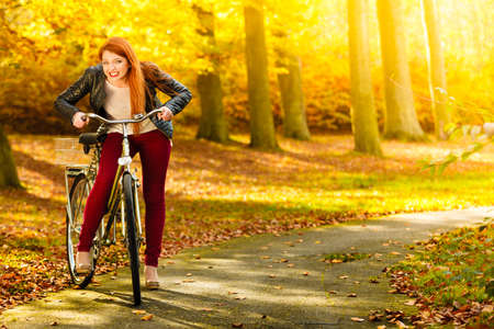 Fall active lifestyle concept,. Beauty young redhaired woman fashion girl relaxing in autumn park with bicycle, outdoor photo