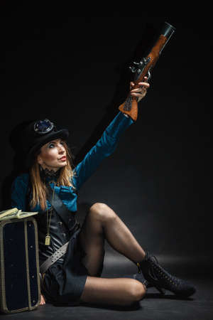 Criminal story bad girl steampunk retro woman with bag suitcase and gun studio shot grunge dark background photo
