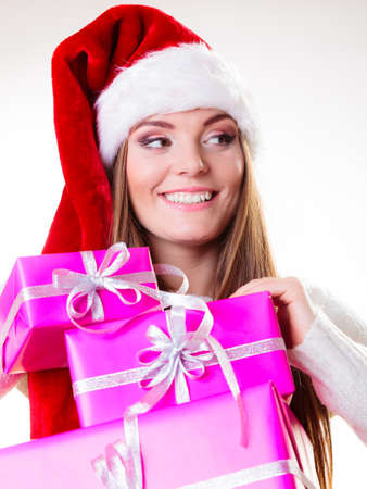 Christmas winter happiness concept. Woman wearing santa helper hat holding stack of pink presents gift boxes isolated on white photo
