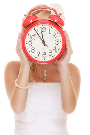 Wedding concept. Time to get married. bride with red alarm clock covering her face isolated photo
