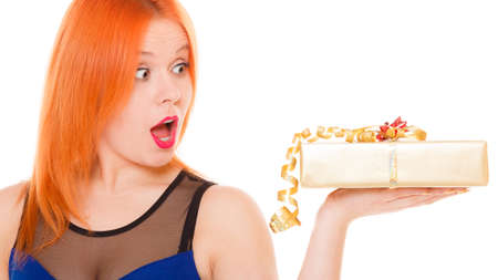 wide eyed: Christmas x-mas winter or valentines day, birthday concept - red hair wide eyed girl holding golden gift box studio shot isolated Stock Photo