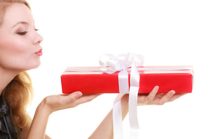 Holidays love and happiness concept - beautiful blonde girl with red gift box blowing a kiss isolated photo