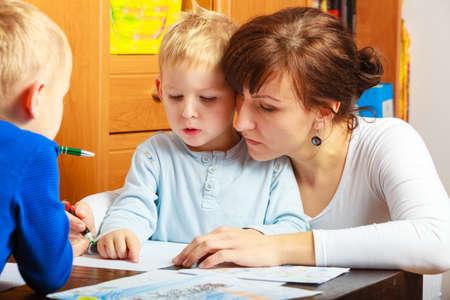 tarea escolar: Familia, los ni�os y la gente feliz concepto. Madre e hijos de dibujo juntos, mam� ayudar con la tarea Foto de archivo