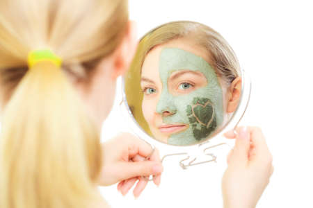 mud woman: Skin care. Woman in clay mud mask on face with heart on cheek looking in the mirror isolated on white. Girl taking care of dry complexion. Beauty treatment.
