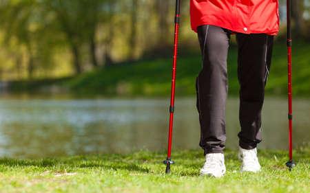 Nordic walking. Close-up van vrouwelijke benen wandelen in het park. Actieve en gezonde leefstijl. Stockfoto
