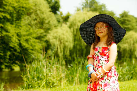 imitate: Cute little girl wearing big summer hat pretending to be woman lady. Child imitate mother playing in park, outdoors Stock Photo