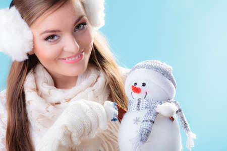 Winter and Christmas time concept. Woman teen girl in warm clothes holding happy nice snowman toy. Studio shot on blue background photo