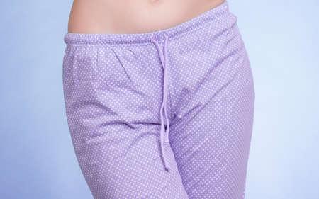 pajama party: Pyjamas pajamas. Closeup of female legs wearing violet pyjama pants on blue. Pajama party at night. Studio shot. Stock Photo