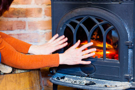 Winter at home. Woman warming her hands at fire fireplace interior. Heating. photo