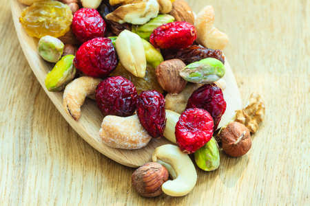 mixed nuts: Healthy food organic nutrition. Closeup different varieties mix of dried fruits and nuts on wooden spoon.