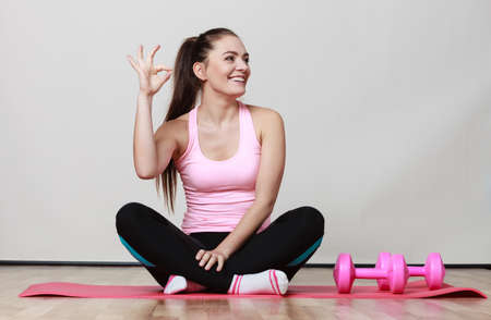 dumb bells: Fitness girl fit woman sitting on exercise mat with dumbbells, doing exercise with dumb bells showing ok sign gray background