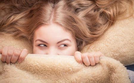 起きてください。朝のベッドの毛布の下で彼女の顔を覆っている女の子を笑って良い夜の睡眠の後幸せに目覚める素敵な若い女性