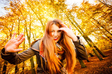 unusual angle: Season and happy people concept. Unusual low angle view of young happy woman in autumn park. Beauty redhaired girl relaxing walking outdoor