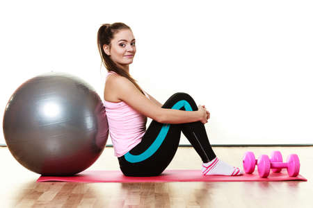 dumb bells: Healthy active lifestyle. Woman with gym ball and dumb bells sitting on exercise mat, isolated on white background