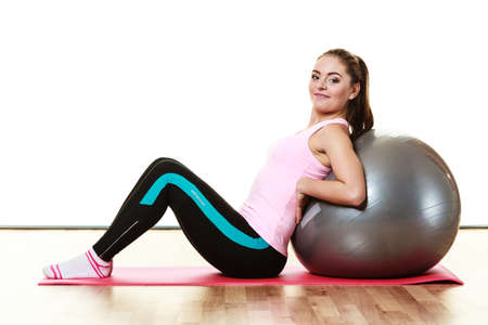 fit ball: sport, training, gym and lifestyle concept. Young happy woman doing fitness exercises with fit ball isolated on white