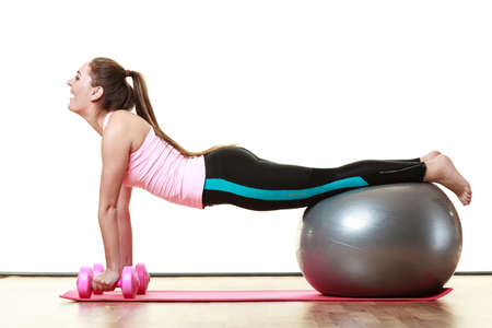 dumb bells: Healthy active lifestyle. Woman with gym ball and dumb bells doing exercise, isolated on white background Stock Photo