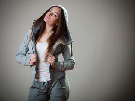 sudadera: Retrato de pelo largo joven muchacha adolescente mujer en la sudadera con capucha sobre fondo gris