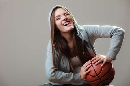 sportingly: Funny sporty woman teen girl long hair holding basketball on gray background