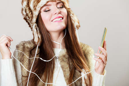 young beautiful woman with smart phone listening music in earphonees. Happy girl in winter clothes fur cap dancing on gray photo