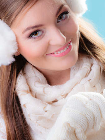 muff: Winter fashion ear protection. Portrait positive teen girl in warm clothes. Happy woman in white earmuffs on blue