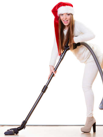 Woman vacuuming the house. Funny girl in santa helper hat with vacuum cleaner. Christmas time and housework concept. photo