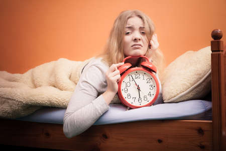 bad girl: Not want to wake up concept. Funny young woman in bed waking up late. Unhappy sleepy girl holds red alarm clock. Stock Photo