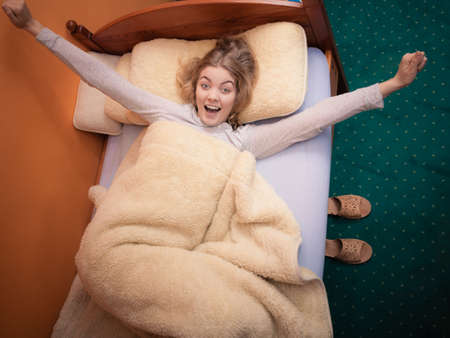 waking up: Wake up. Lovely young woman waking up happily after good night sleep, stretching in the morning in bed.